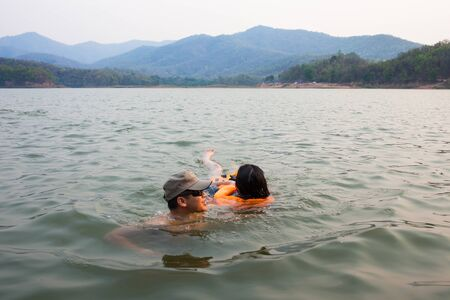 Phayao, Thailand - April 15, 2016. Man at river help women drowning due to water accidents by wearing a life jacket and escorted out of the water .