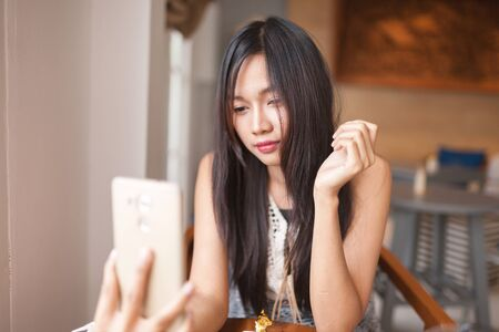capture: Home, technology and lifestyle concept - A women using smartphone for capture selfie .