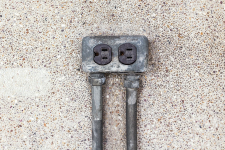 standard steel: Asia plug socket on brick wall background. Risk of danger. Stock Photo