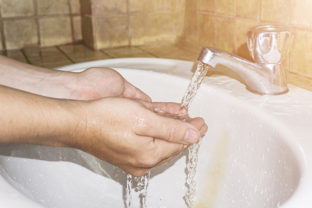 Boy washes hands with running water.