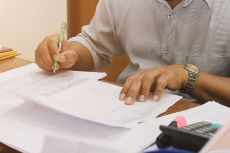 freelancing: Close-up of business man hand writes a pen in a paper.