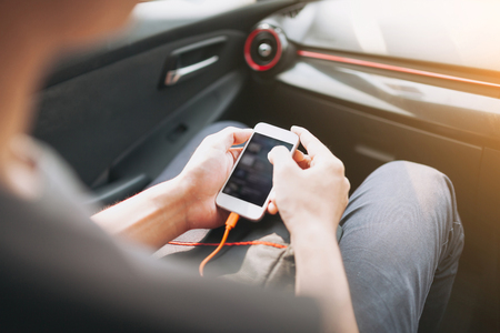 software portability: Man connecting phone to the car media system.