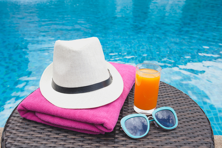 Summertime orange juice hat and sunglasses relax near swimming pool. Stock Photo