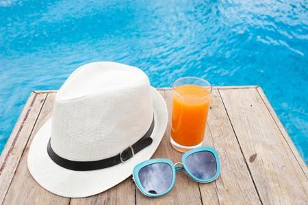 Summertime orange juice hat and sunglasses relax near swimming pool. Stock Photo