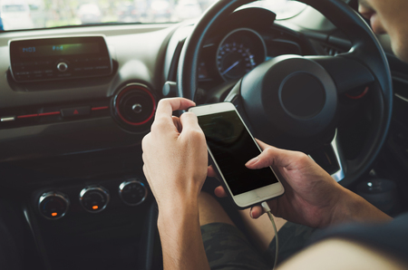 software portability: Man using phone in the car. Stock Photo