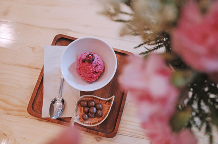 Chocolate ice cream in a glass cup with flower on wood table. Stock Photo