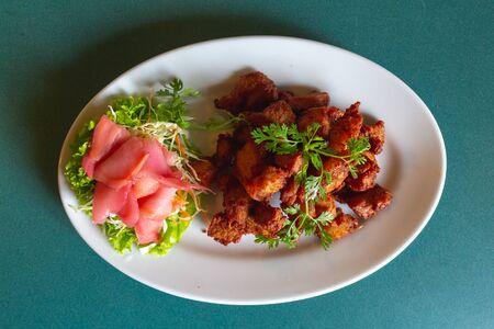 Deep fried pork three big soya sauce with vegetables on whites dish.