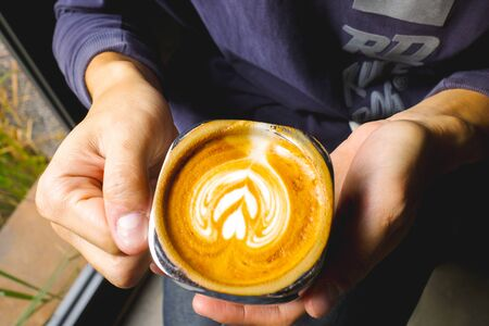 Close-up of man holding a hot latte coffee. Archivio Fotografico - 138043414
