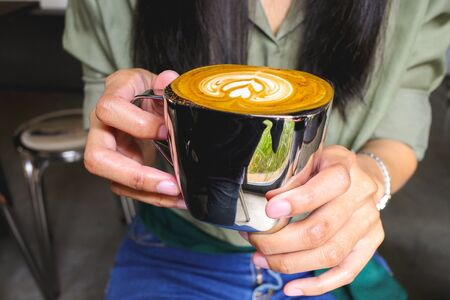 Close-up of women holding a hot latte coffee.