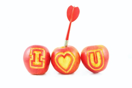 Fresh red apple with I love you shaped cut-out and arrow on white background photo