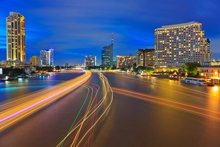 praya: lights line of boats on the Chao Praya River at dusk , Bangkok, Thailand