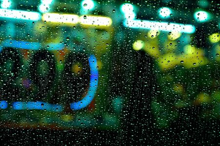 rain drop on glass and colorful night light photo