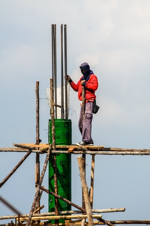 the worker with pillar on high place Editorial