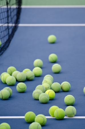 tennis balls rests next to the net on a tennis court