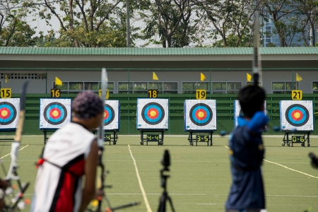 bull s eye: An archer with bow takes aim at a target during competition Stock Photo