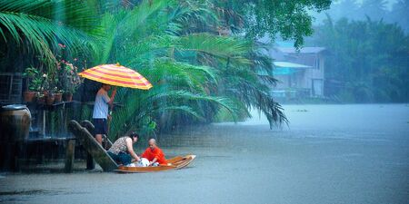 People give food offerings to a Buddhist monk coming by boat, in the morning rain  Amphawa, Thailand