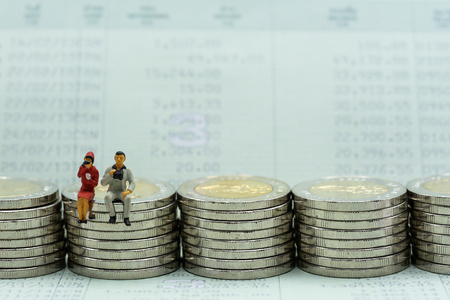 Money laundering concept. Miniature people, officer investigating coins stacks and customer statment. Stock Photo