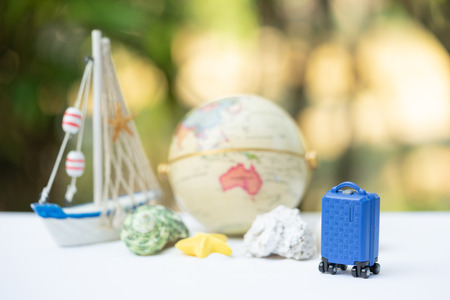 Travel and financial saving concept. Miniature baggage on the sandbox decorating for summer. Reklamní fotografie