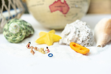 Miniature people, travelers relaxing on the sand box decorating in summer theme using as background travel, exploring the world, budget trip concept. 写真素材