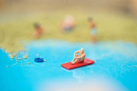 Miniature people, travelers kayaking in the sand box decorating in summer theme using as background travel, exploring the world, budget trip concept.