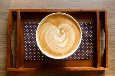 Latte bowl with tulip art on a wooden tray photo