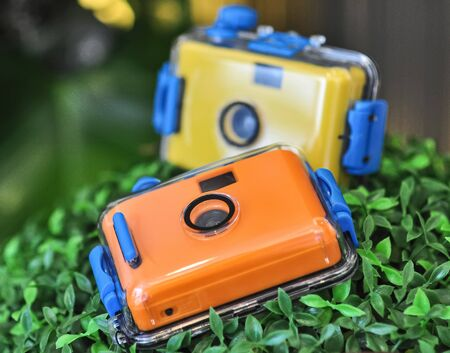 Waterproof underwater camera orange and yellow color on fake bush