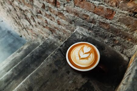 Coffee cup with latte art on the stairs.