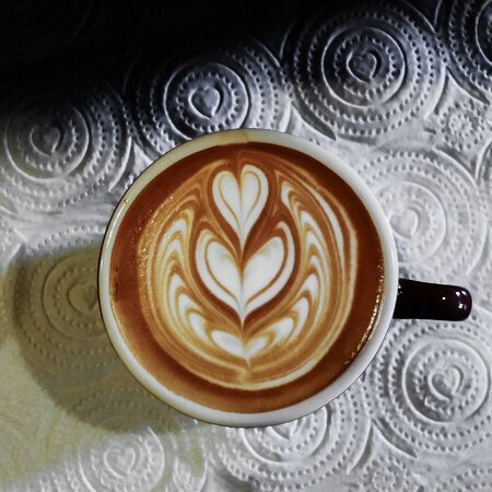 Coffee cup with latte art on the abstact backgound.