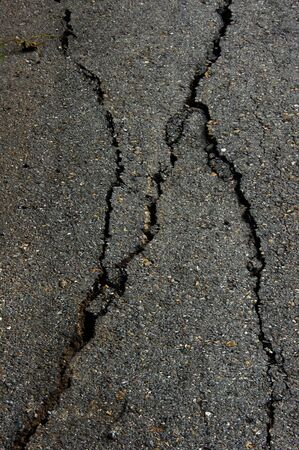 Cracked road on asphalt close up photo