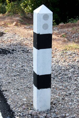 Stone pillars prevent accidents on the road curved  photo