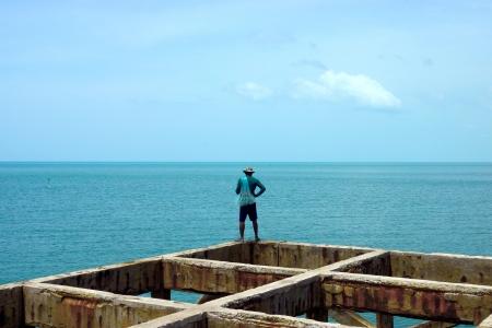 fishingpole: Fishermen are fishing on old harbor at the sea.