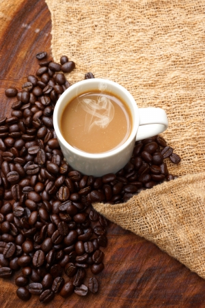 Coffee and beans on the wooden background.