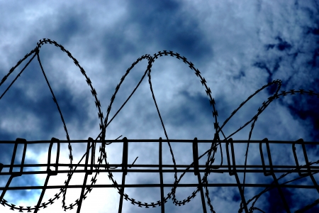 Barbed wire on dark fence. silhouette photo photo