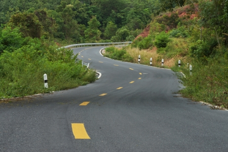 seson: Empty curved road to the mountain. Stock Photo