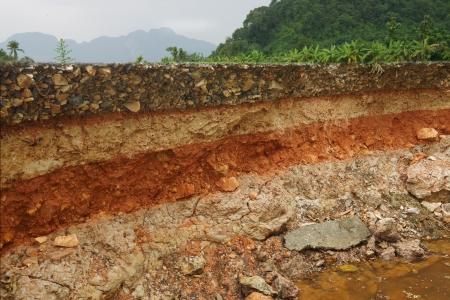 De stoeprand erosie tegen stormen Om de lagen van de bodem en rock geven Stockfoto