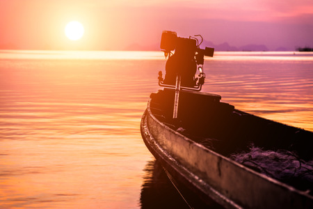 silhouettes fishing boat on sunset sky beautiful lagoon photo