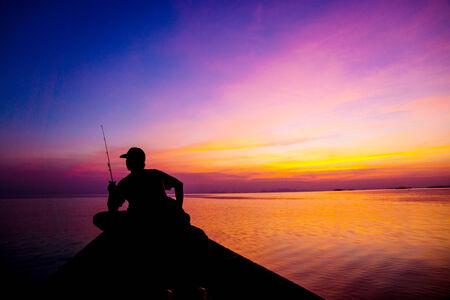 Lonely man fishing silhouettes on sunset sky beautiful lagoon photo