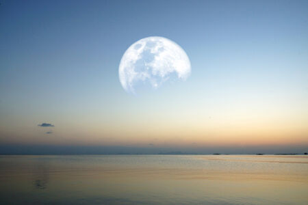 moon on lake with blue sky and colorful sunset Stock Photo