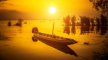 Silhouettes fishing boats on the lake. photo