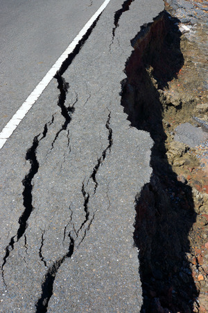 Fissures and erosion of the asphalt road by the earthquake. photo