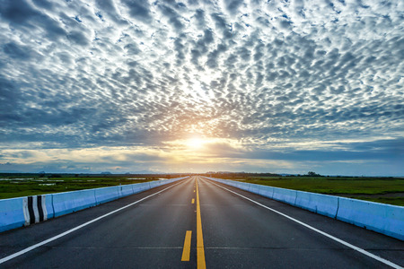 dividing lines: Empty road and the yellow traffic lines with clouds.