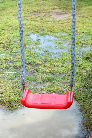red chain swings on modern kids playground in rainy day. photo