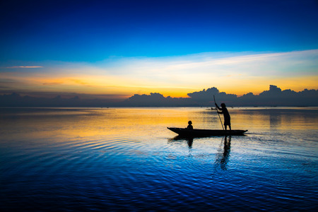 Beautiful sky and Silhouettes of fisherman at the lake, Thailand. photo