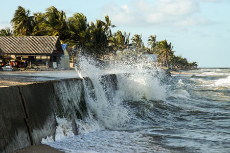NAKORN SRI THAMMARAT THAILAND - January 11 : Raging waves to shore, and the houses of the fishermen. on Jan. 11, 2015 in Nakorn sri thammarat, Thailand. photo