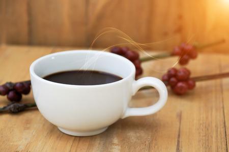Hot coffee on the wood and raw coffee bean. photo