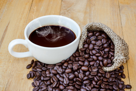 Hot coffee on the wood and roast coffee bean. photo