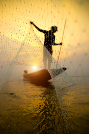 Silhouettes fisherman throwing fishing nets during sunset, Thailand.
