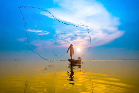 Silhouettes fisherman throwing fishing nets during sunset, Thailand. photo