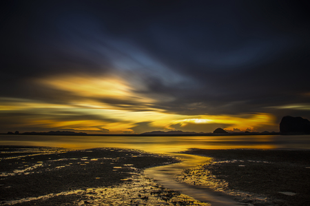 Silhouettes of Beautiful golden sunset in the sea with saturated sky and clouds. photo
