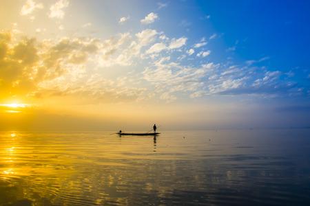 pescador: Hermoso cielo y siluetas de pescador en el lago, Tailandia.